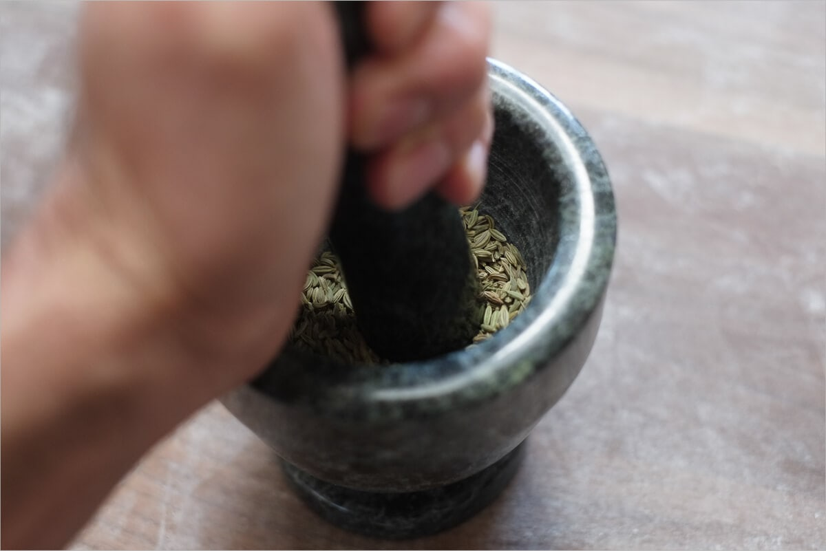 Crushing fennel seed with mortar & pestle