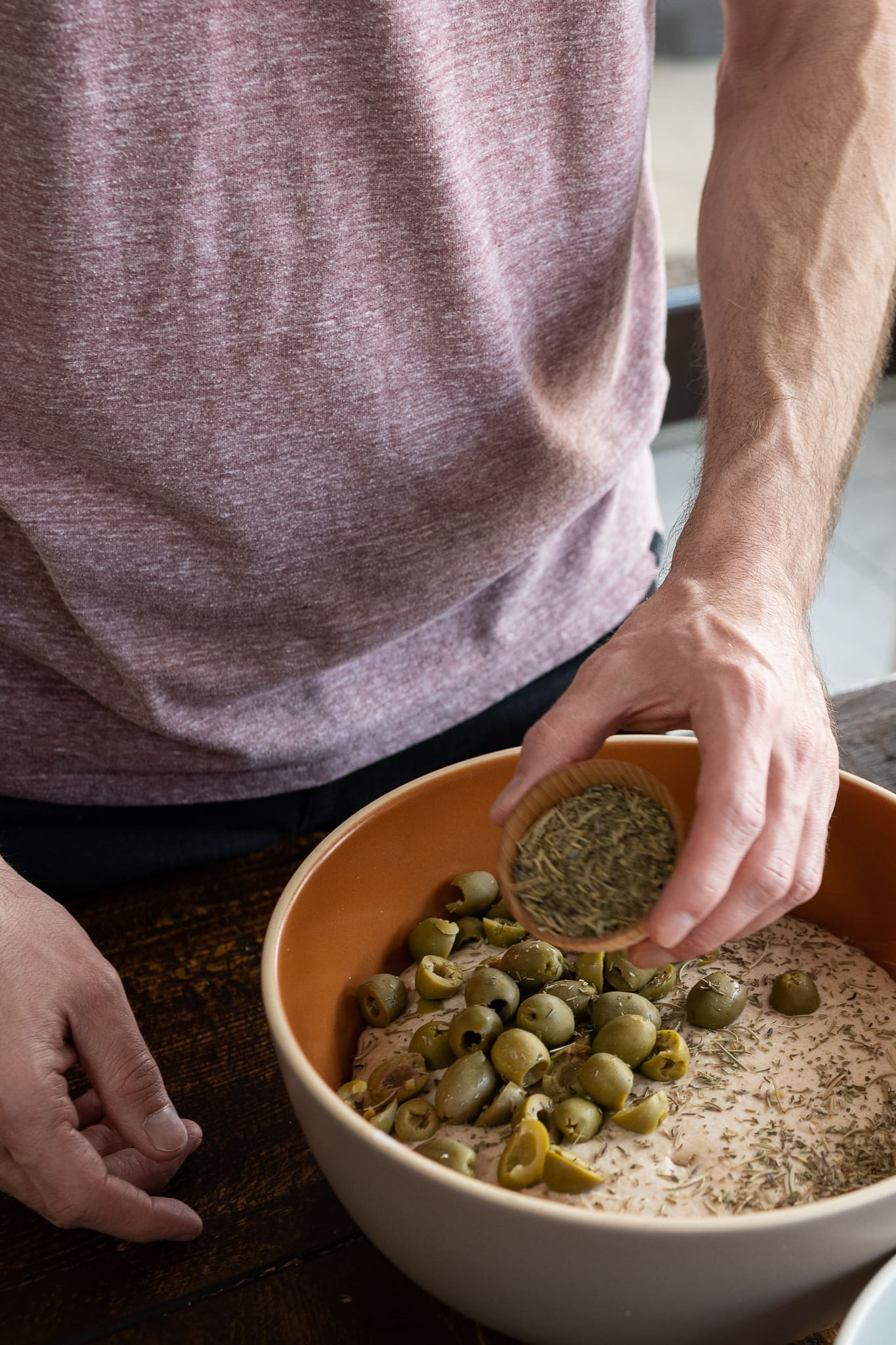 Adding herbes de Provence to green olive and herb sourdough bread