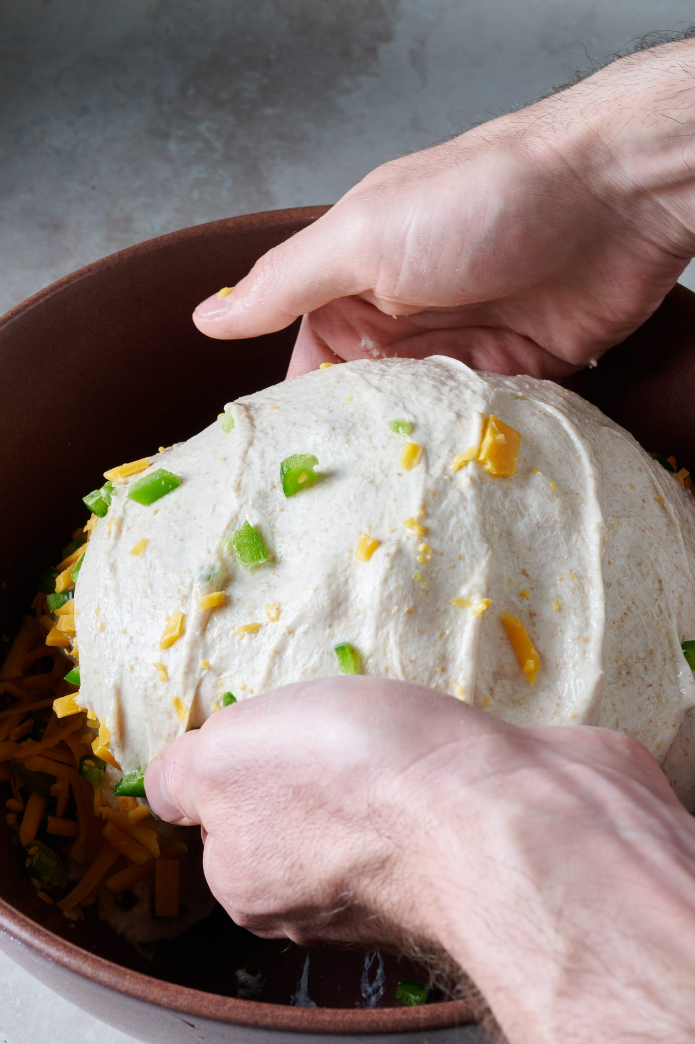 Adding jalapeño and cheddar cheese to dough during bulk fermentation